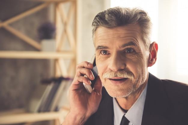 Homem em roupas clássicas está falando no telefone celular