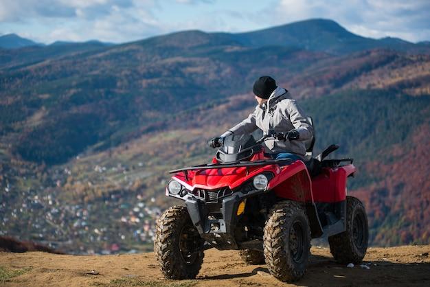 Homem em roupas de inverno em uma moto-quatro vermelho no topo de uma montanha