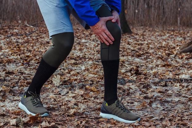 Homem em roupas de treino sofreu uma lesão no joelho enquanto fazia jogging ao ar livre. conceito de lesão esportiva, técnica de corrida, corrida errada, tendinite, uma grande carga.