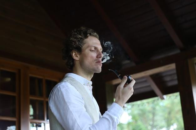 Homem em roupas elegantes, fumando um cachimbo liberando fumaça fora da residência