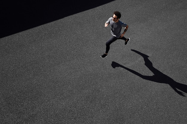 Homem em roupas esportivas correndo na estrada