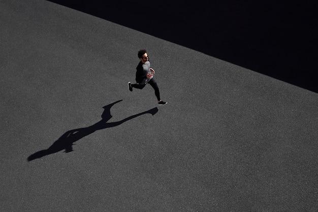 Homem em roupas esportivas correndo na vista de cima da estrada