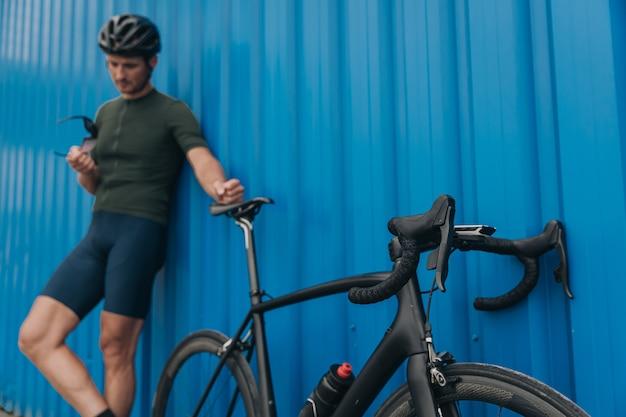 Homem em roupas esportivas e capacete em pé ao ar livre com uma bicicleta