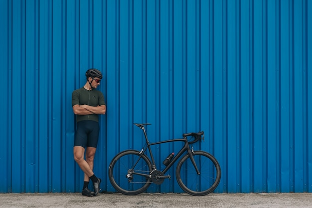Homem em roupas esportivas olhando para a bicicleta em pé ao ar livre