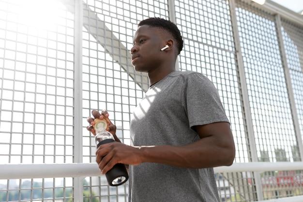 Homem em roupas esportivas segurando uma garrafa de água