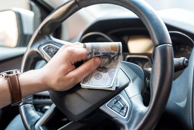 Homem em seu carro conta para nós contas de dinheiro para conceito de financiamento de pagamento