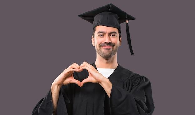 Homem em seu dia da formatura universidade fazendo símbolo do coração pelas mãos. estar apaixonado