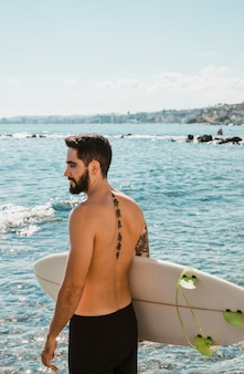 Homem, em, shorts, ficar, com, branca, surfboard, ligado, praia