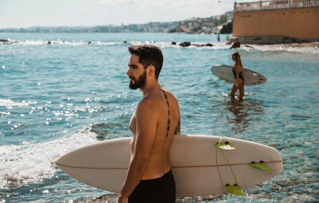 Homem, em, shorts, ficar, com, surfboard, em, mar