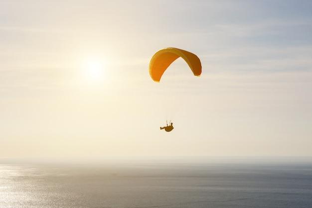 Homem em silhueta de parapente voando sobre o mar