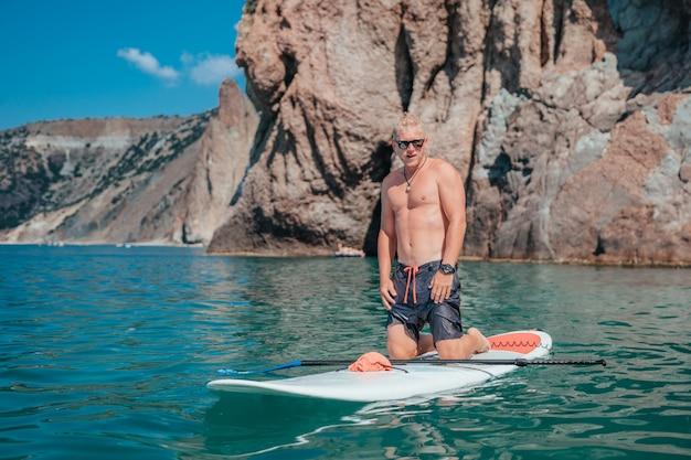Homem em stand up paddleboard no mar