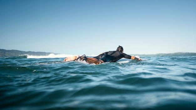 Homem em sua prancha de surfe nadando de longe