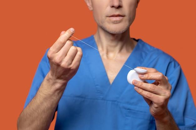 Homem em terno médico mostrando fio dental