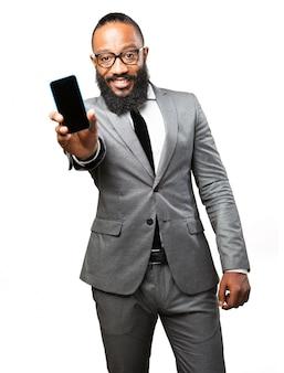 Homem em terno mostrando um telefone