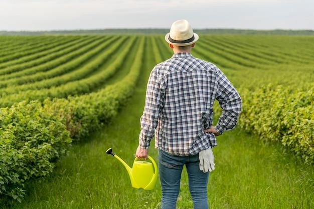 Homem em terras agrícolas com regador