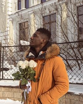 Homem em tiro médio segurando um buquê de flores