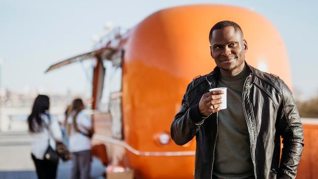 Homem em tiro médio segurando uma xícara de café na frente do caminhão de comida