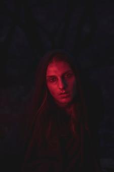 Homem em tons de luz vermelha, sentado no escuro