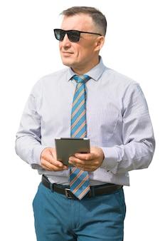 Homem em traje de negócios com tablet na mão, olhando para o lado em fundo branco isolado