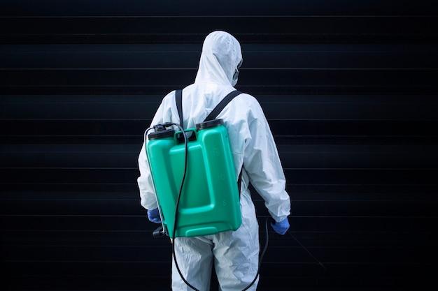 Homem em traje de proteção branco com reservatório para pulverização e desinfecção