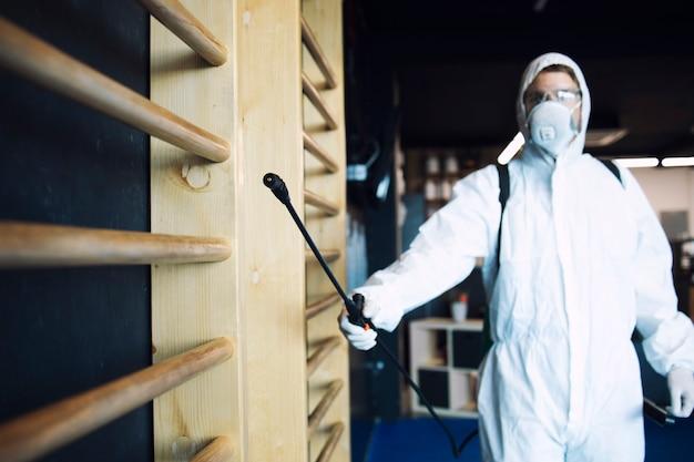 Homem em traje de proteção branco desinfetando e equipamentos de ginástica e pesos para impedir a propagação do vírus corona altamente contagioso