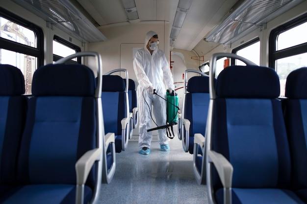 Homem em traje de proteção branco, desinfetando e higienizando o interior do trem do metrô para impedir a propagação do vírus corona altamente contagioso