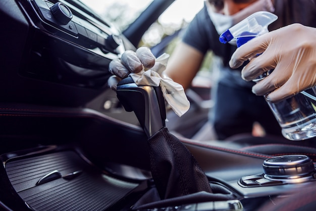Homem em traje de proteção com máscara desinfetante dentro do carro, limpe as superfícies que são tocadas com frequência, evite infecção de coronavírus, contaminação de germes ou bactérias. infecção