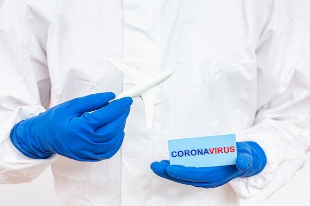 Homem em traje de proteção com sinal de coronavírus
