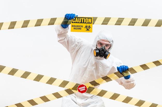 Homem em traje de proteção com sinal de perigo