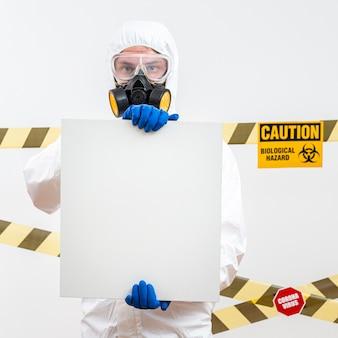 Homem em traje de proteção com um sinal em branco