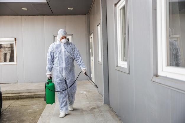 Homem em traje de proteção contra vírus e máscara de desinfecção de edifícios de coronavírus com o pulverizador. epidemia.