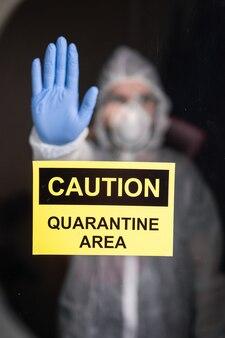 Homem em traje de proteção e máscara médica protetora, mostrando o gesto de parada. epidemiologista mostra gesto não