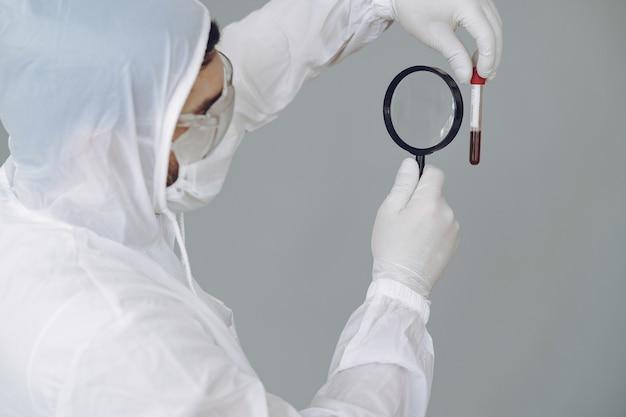 Homem em traje de proteção e óculos na parede cinza