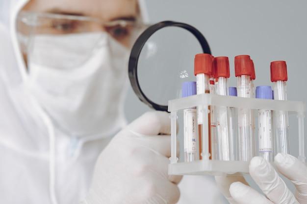 Homem em traje de proteção e óculos trabalhando no laboratório