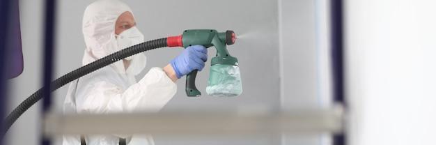 Homem em traje de proteção e respirador pulveriza tinta nas paredes.