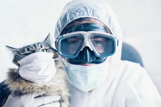 Homem em traje de risco biológico e gatinho com máscara de proteção