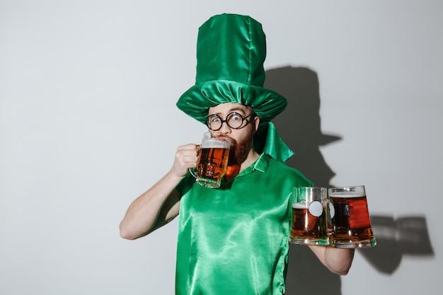 Homem em traje de st.patriks, bebendo cerveja e segurando copos