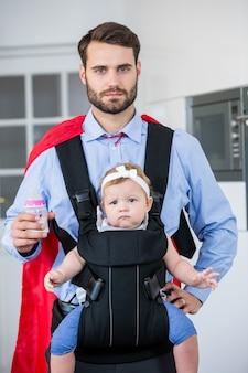 Homem em traje de super-heróis, carregando a filha