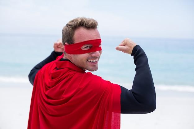 Homem em traje de super-heróis, flexionando os músculos na beira-mar