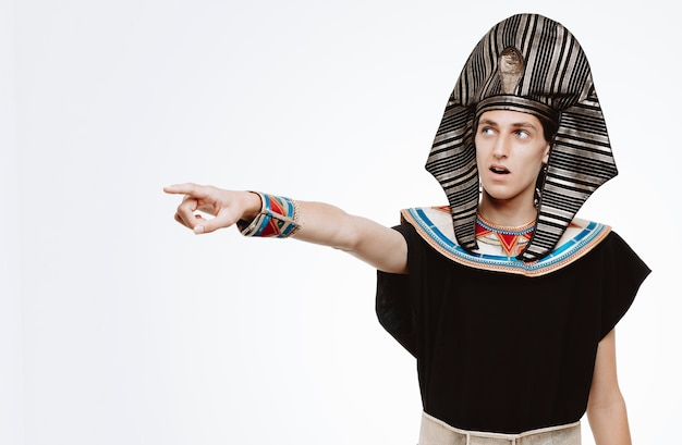 Homem em traje egípcio antigo olhando para o lado e ficando intrigado apontando com o dedo indicador para algo em branco