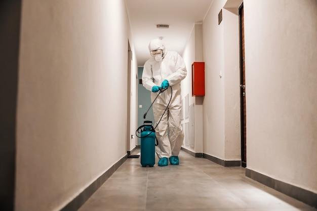 Homem em traje estéril, desinfetando o corredor do edifício. proteção do conceito de corona.