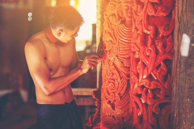 Homem em traje tradicional estilo antigo com ferramenta de gravura criar a escultura de vela