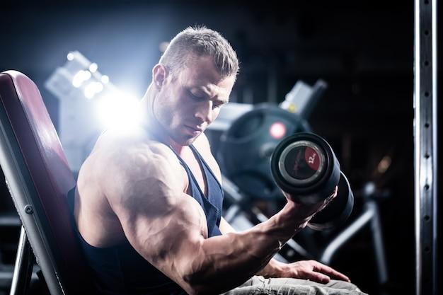 Homem, em, treinamento aptidão, com, dumbbells, em, ginásio