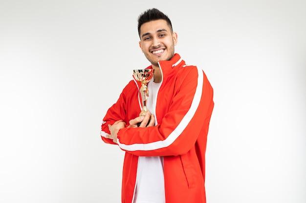 Homem em um agasalho vermelho mostra a taça de ouro do vencedor em um branco