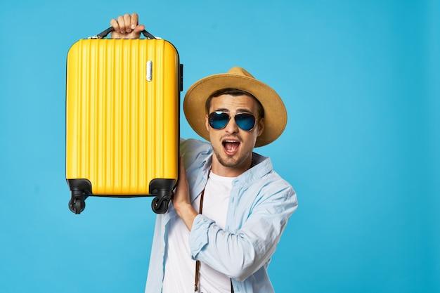 Homem em um azul com óculos e uma mala amarela
