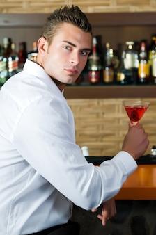 Homem em um bar com martini vermelho em um bar