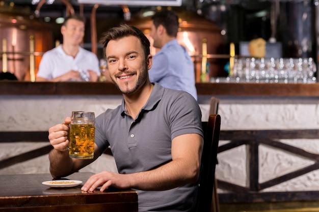 Homem em um bar de cerveja. jovem alegre segurando uma caneca de cerveja e sorrindo enquanto está sentado no bar