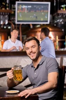 Homem em um bar de cerveja. jovem bonito segurando uma caneca de cerveja e sorrindo enquanto está sentado em um bar