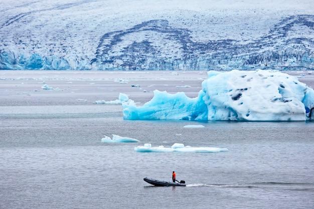 Homem em um barco a motor veloz navegando em uma lagoa glaciar na islândia