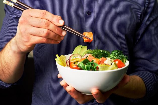 Homem, em, um, camisa, segura, cutucar tigela, com, salmão, abacate, pepinos, rúcula, brócolos, com, chopsticks